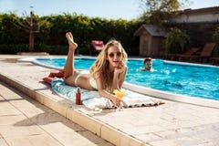 Коктеиль красивой белокурой девушки выпивая, загорать, лежа около бассейна Стоковые Фото