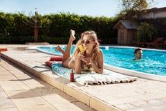 Коктеиль красивой белокурой девушки выпивая, загорать, лежа около бассейна Стоковая Фотография RF
