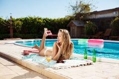 Коктеиль красивой белокурой девушки выпивая, загорать, лежа около бассейна Стоковое Фото