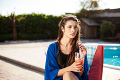 Коктеиль красивой девушки брюнет выпивая, сидя около бассейна стоковое фото rf