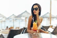 Коктеиль красивой девушки выпивая на пляже Стоковые Изображения