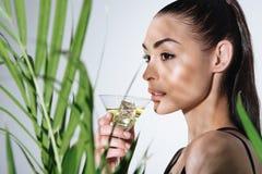 Коктеиль молодой женщины брюнет выпивая и представлять около зеленой ладони выходят Стоковая Фотография