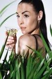 Коктеиль молодой женщины брюнет выпивая и представлять около зеленой ладони выходят Стоковое Изображение RF