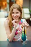 Коктеиль молодой женщины выпивая в кафе Стоковые Фотографии RF