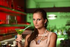 Коктеиль довольно молодой женщины брюнет выпивая в баре Стоковая Фотография