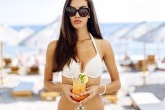 Коктеиль сногсшибательной женщины выпивая на пляже Стоковые Изображения