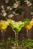 3 коктеиля: ананас, апельсин, киви безалкогольный напиток плодоовощ с льдом на деревянной предпосылке и цветках Стоковые Фото