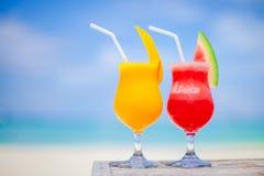 2 коктеиля арбуза и манго на предпосылке сногсшибательного моря бирюзы Стоковые Изображения