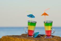 2 коктеиля при соломы стоя на утесе против моря Стоковые Изображения RF