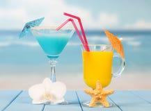 2 коктеиля с зонтиками закрывают вверх на предпосылке моря Стоковая Фотография