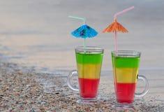 2 коктеиля с соломами в песке на seashore Стоковая Фотография RF