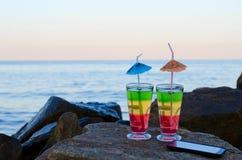 2 коктеиля с соломами и smartphone на камнях пляжа Стоковые Фотографии RF