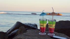 2 коктеиля с соломами и smartphone на утесах Прибрежный, шлюпка плавает на заднем плане акции видеоматериалы