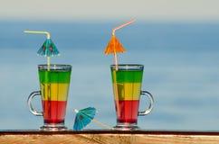 2 коктеиля с соломами на баре на заднем плане моря в расстоянии Стоковые Изображения