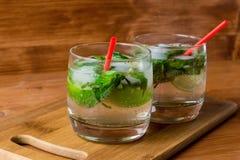 2 коктеиля mojito с льдом в стекле на таблице Стоковые Фото