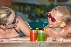 Коктейли матери и сына выпивая в бассейне Горячие летние отпуска стоковые изображения