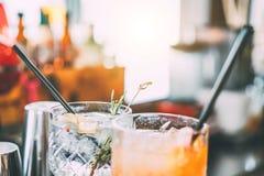 Коктейли служат на счетчике бара подготовленном с джином, розмариновым маслом, papper и апельсиновым соком - напитком, ночной жиз стоковые фото