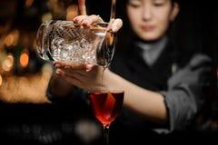 Коктейль алкоголя женского бармена лить используя стрейнер стоковая фотография