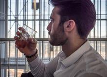 Коктейль молодого бизнесмена выпивая стоковое фото rf