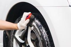 Колеса автомобиля человека чистя щеткой, резиновая чистка Стоковые Фото