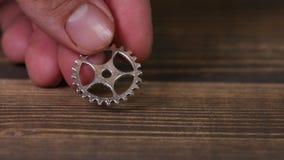 Колеса шестерни на деревянном столе сток-видео