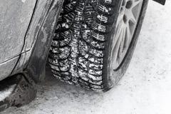 Колесо автомобиля на автошине снега с стержнями металла Стоковые Фотографии RF