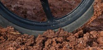 Колесо мотоцикла на влажной грязи почвы после идти дождь в сезоне дождей в дороге сельской местности Стоковые Фотографии RF