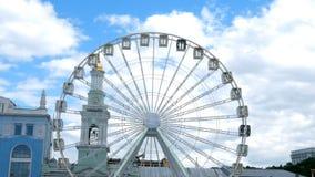 Колесо ferris конца-вверх большое белое вращает в городе Киева, Украине, на квадрате Contractova сток-видео