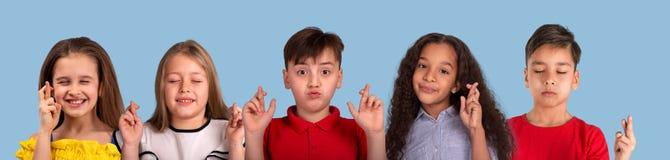 Коллаж портретов эмоции студии Мульти-этнической группы в составе школьник, на голубой предпосылке стоковые изображения