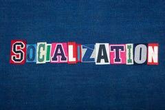 Коллаж СОЦИАЛИЗАЦИИ текста слова, multi покрашенная ткань на голубой джинсовой ткани, социально опытная и концепции доверия стоковые изображения