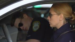 Коллега и оба женщина-полицейского ждать мужской управляя прочь, патрулирующ территорию сток-видео