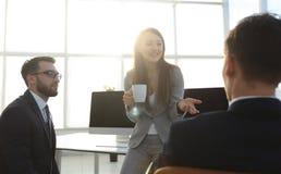 Коллеги беседуя пока наслаждающся перерывом на чашку кофе в офисе Стоковое Изображение