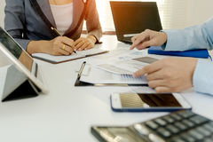 2 коллеги бизнесмена обсуждая данные по диаграммы плана финансовые на таблице офиса с компьтер-книжкой и цифровой таблеткой Дело  Стоковая Фотография RF