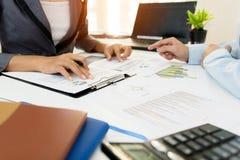 2 коллеги бизнесмена обсуждая данные по диаграммы плана финансовые на таблице офиса с компьтер-книжкой Стоковая Фотография
