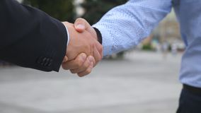 Коллеги встречают и трясут руки в предпосылке города 2 бизнесмена приветствуя один другого в городской среде Стоковое фото RF