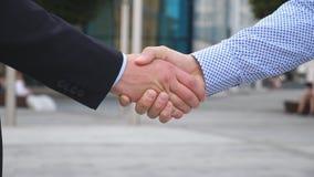 Коллеги встречают и трясут руки в предпосылке города 2 бизнесмена приветствуя один другого в городской среде Стоковые Фотографии RF