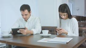2 коллеги в кафе занятом при их устройства не смотря один другого Стоковое Изображение