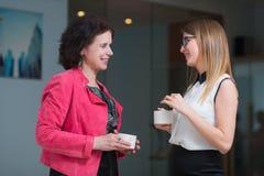 Коллеги в офисе говоря друг к другу во время перерыва на чашку кофе Стоковые Фото