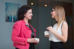 Коллеги в офисе говоря друг к другу во время перерыва на чашку кофе Стоковое фото RF
