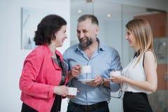 Коллеги в офисе говоря друг к другу во время перерыва на чашку кофе Стоковое Изображение RF