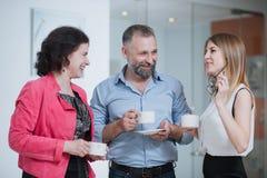 Коллеги в офисе говоря друг к другу во время перерыва на чашку кофе Стоковые Изображения