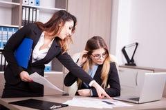 2 коллеги в офисе говоря пока один показывает другой t Стоковые Изображения RF