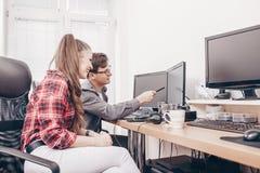 Коллеги в офисе работая на настольном компьютере стоковое изображение