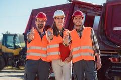 Коллеги в транспортно-экспедиционной компании перевозки давая большие пальцы руки вверх Стоковая Фотография