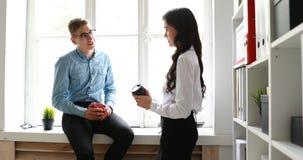 Коллеги говоря и выпивая кофе пока на окне в офисе сток-видео