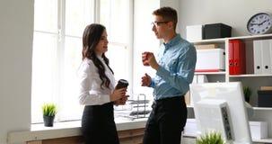 Коллеги говоря и выпивая кофе пока на окне в офисе акции видеоматериалы