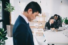 коллеги дела в современном офисе с подавленным азиатским бизнесменом стоковые фото