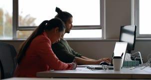 Коллеги дела используя ноутбук и сочинительство на дневнике на столе 4k сток-видео