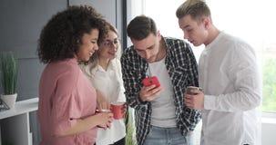Коллеги дела наслаждаясь содержанием средств массовой информации на мобильном телефоне видеоматериал