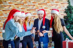 Коллеги дела на рождественской вечеринке офиса владение домашнего ключа принципиальной схемы дела золотистое достигая небо к Стоковые Фото
